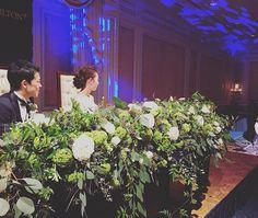 wedding repo11 高砂のお花の雰囲気がわかる写真です❤️ 会場に合うように落ち着いたイメージにしたくて、緑と白を基調としました。 * * お花は#ラナンキュラス #トルコききょう と#ミニバラ * * 緑は紫陽花を含めて、葉物を入れてもらいました❤️ * * この時期はなかなか手に入らない実を入れたくて探していただきギリギリに#エリンジウム を追加✨これでぐんと雰囲気が出ました♪ * * 各卓装花はこれだけだと寂しいので紫の花をポイントにいれました。 お花はhanahiroさん担当♪ありがとうございました❤️ * * #高砂 #高砂装花 #装花 #wedding #プレ花嫁 #卒花 #結婚式 #weddingflower #flower