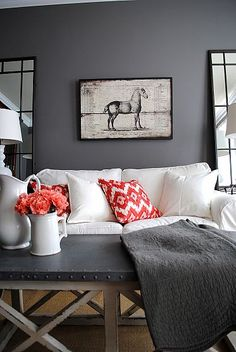 Living room with charcoal walls. Love the dark color with the red punch