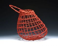 Woven onion basket designed for air to circulate around the onions so they can breath. Also could be hung in a bathroom with soap balls.. Empty, it serves as wall art. One was sold several years ago for a man to put his golf balls in. I sometimes fill mine with seashells.  It can sit on a counter or hang on a cup hook.  Twined and dyed with iron oxide dye. Other colors available by special order.  Measures approximately 10 x 9 x 8.5  This is a stock photo. Each basket is individually crafted…