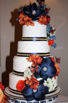 Silk flowers adorn this 4 tier wedding cake.....burnt orange and navy blue were the main colors of the wedding party