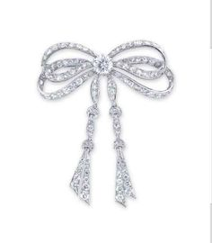 A DIAMOND BROOCH -  The old European and single-cut diamond ribbon, set to the centre with a brilliant-cut diamond, mounted in 18k white gold, 6.9 cm long
