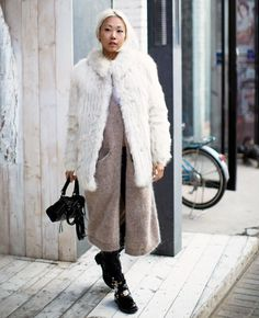 The Haute Pursuit in a fur jacket layered over a long wool cardigan and patent chunky boots