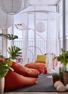 A small balcony furnished with orange beanbags, green plants, cushions and a large mosquito net.