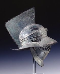 Side view of a bronze gladiator's helmet. Said to be found at the gladiators' barracks at Pompeii . Roman, 1st Century CE. British Museum