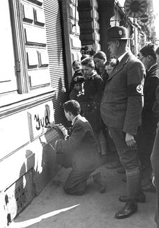 Vienna, Austria, 1938, A Jew forced to write antisemitic slogans on a wall.
