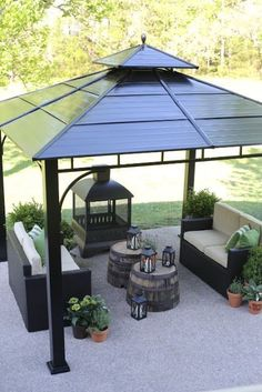 Anchor your outdoor space with a gazebo that provides shelter for a comfortable seating area and cozy fireplace. Groupings of plants and lanterns soften this backyard gathering area.