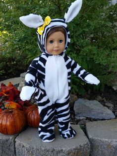 Its a Zoo Zebra is perfect for Halloween for your 18 inch doll. It features zebra print soft fluffy fleece with a contrasting white fleece front placket, ears, inside of hood, paws and soles of feet. It is a one piece footie style pajama or costume. It closes with a zipper in the front.