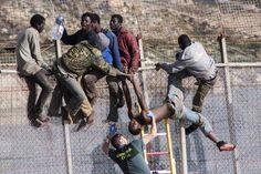 Un inmigrante africano es separado de la valla que divide la frontera entre España y Marruecos en Melilla [Imagen: palitroque1 Flickr]