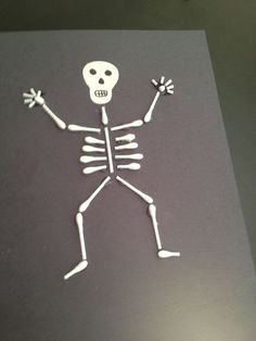 """the glueing was a little difficult for albert. if we did this for preschool, I may pre-glue the """"bones"""" to black paper, then have the kids assemble the pieces together."""
