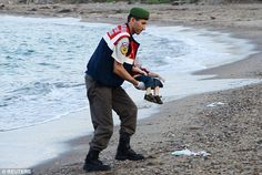 The human cost: A policeman on a Turkish beach gently recovers the bodies of two brothers drowned as their family tried to make their way to the Greek Island of Kos