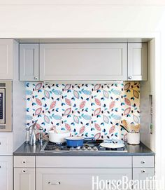 Sandwiched between glass, a piece of Lee Jofa's Lauretta fabric becomes a delightful accent in an English country-style kitchen. Click through for more kitchen backsplash ideas.