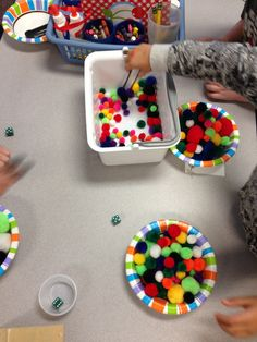 Kindergarten fine motor math center: roll a 6-sided die and grab that number of pom poms with tongs.