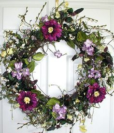 """Price: $89.99 This beautiful wreath is a versatile creation that can be used for more than one season. Hang it up in spring and summertime, and it will be admired for its refreshing colors. Display it in the fall and early winter, and you will see how it brightens up your days with purple dahlias, lavender hydrangea clusters and tiny yellow wildflowers. How could we ask for more? Hang it up where ever you desire and enjoy it all year long! Measures 22""""W x 5""""D, ground ships for free!"""