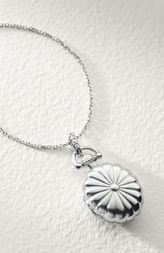 This locket, forged of sterling silver, hangs off a 17 inch chain and features a scalloped design with white sapphire accents on the bail. A perfect piece to hold memories close to your heart.