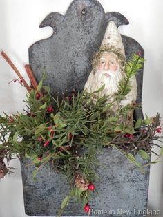 Santa and greenery with cinnamon sticks and berries in a wall bin/container.