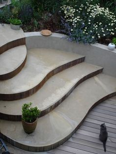Concrete steps flowing into the curved retaining wall.