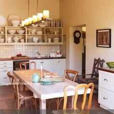 Die Fliesen und das offene Wandregal lassen diese ländliche Küche kühl und strukturiert wirken. Ein großer Kerzenleuchter als Deckenleuchte und die rustikalen…