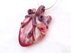 This one of a kind creation is going to be your new favorite piece of jewelry. Maroon and purple ventricles over a large multi colored base make this an eye catching anatomical heart borosilicate glass pendant. This stunning lampwork borosilicate glass pendant is created without molds and is a one of a kind work. Item Specifications  Pendant is 2 1/4 inches in length and 1 1/2 inches in width (each piece may vary slightly).  Available finished as shown on an 18 inch sterling silver ...