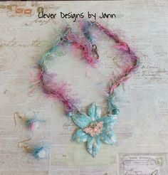 July's Challenge .. BoHo Flower Necklace .. A large B'sue flower is painted using Turquoise and Ivory Iced Enamels .. a B'sue Butterfly sits in the center of the flower .. Brass chain and Fun Fur (eyelash yarn) complete this necklace .. matching earrings .. Jann Tague .. Clever Designs .. https://www.facebook.com/JewelsByJann