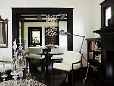Love the white cream paint wall colors with dark floors and black molding! Fantastic mid-century modern living room design with ebony stained trim. Black painted fireplace and built-ins shelves cabinets. Black wood floors! Modern floor lamp, glass canisters vases, modern chandelier and modern dining room furniture. Black moldings, black trim,