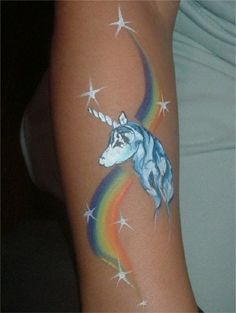 A unicorn tattoo with the rainbow and stars. The simple unicorn head is drawn above a streak of rainbow colors and surrounded by glinting stars.