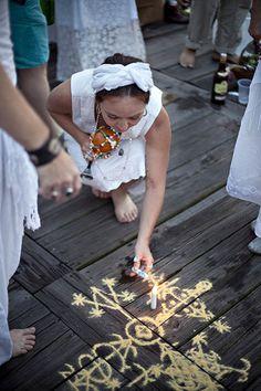 Lighting a candle over a Veve A priestess lights a candle over a veve during a…