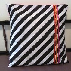 Housse de coussin graphique rayée noir et blanc et rubans rouge, rose, orange
