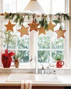 Хвойные веточки и звездочки украшают кухонное окно, цветочные горшки завернуты в красную ткань. .