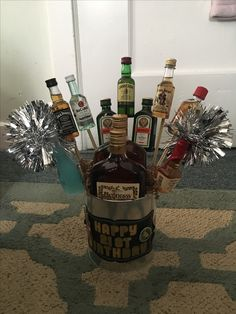21st Birthday Present - Galvanized milk jug with bottles of alcohol. The mini bottles are taped to doubled skewers which were shoved in a styrofoam ball. Decorative shred covered the hole. Message was made from chalkboard sticker and scrapbook stickers. The gold trimming is made from crafting tape.