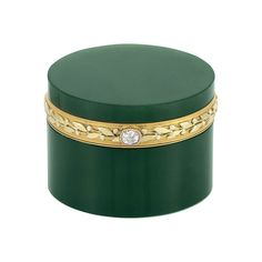 Antique Nephrite, Two-Color Gold and Diamond Box 18 ct., the round box centering a gold band with a garland motif, with one oval old-mine cut diamond thumbpiece, with maker's mark, circa 1890. 1 7/16 x 1 7/16 x 1 1/16 inches.