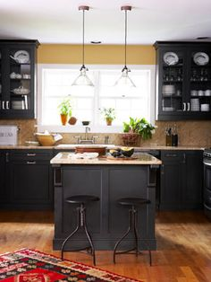 A Black and Gold Kitchen    Gold-flecked granite tops black cabinetry in the kitchen; the draftsman stools are from Wisteria Home. Open white windows keep the room from feeling too dark.      Read more: Kitchen Designs - Pictures of Kitchen Designs and Decorating Ideas - Country Living
