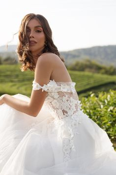With off-the-shoulder straps and a floral lace body, the Diana dress from Mila Bridal is strikingly romantic. This gown features a zipper back and an invisible inner corset for good support of your bust and waist. #weddingdress #floralweddingdress #weddinggown #simpleweddingdress
