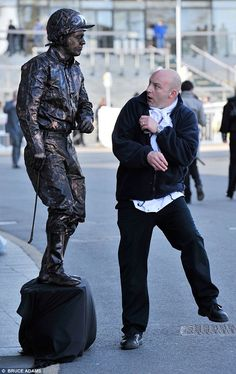 This jockey living statue scared a passer-by on the first day of the Grand National at Aintree, Liverpool