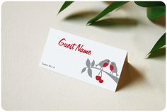 Song Birds - Place card featuring two red-breasted love birds perched on a gray branch with heart-shaped cherries. Your guest's name and table number are printed on both sides of the fold. Change the design colors with our complimentary service. Available from Urbanity Studios.