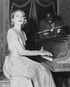 Medium BTS shot of Grace Kelly as Tracy Samantha Lord playing piano as Louis Armstrong as Himself holding trumpet, looks on.