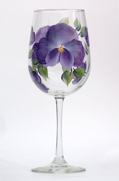 Deep purple pansy petals with white highlighting and deep green leaves hand-painted on quality 18.5 ounce wine glass.