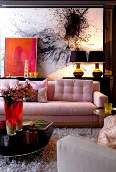Living Room Ideas. Walls painted black, pink sofa, shag rug, round coffee table, oversized abstract art, smaller abstract art leaning.