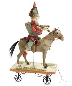 """*FRENCH BISQUE PULL-TOY """"POLICHINELLE ON HORSE"""" ~ 17"""". posed upon a wooden platform w/metal spoked wheels is a bisque head Polichinelle seated upon a paper mache horse w/ flocked finished... When pulled along, Polichinelle turns his head from side to side + waves the whip he holds in his hand. Marks: F.G. (in scroll). Comments: the doll by Gauthier, the maker of the classic pull-toy is unknown, c.1890."""