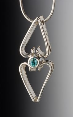 BLUE ZIRCON ON PIERCED STERLING SILVER. HAND FORGED