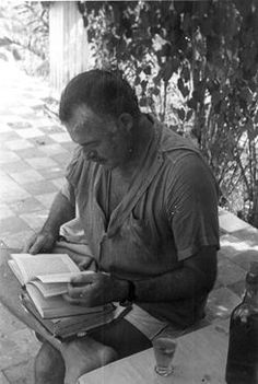 Ernest Hemingway reading outside his home, Finca Vigia, San Francisco de Paula, Cuba. Credit Line: Ernest Hemingway Collection. Kennedy Presidential Library and Museum, Boston.
