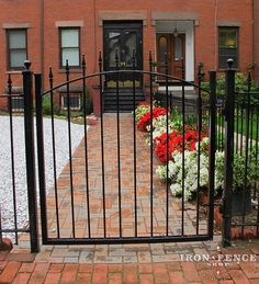4x4 arched wrought iron gate and fence in a front garden area