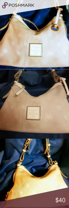 Dooney & Bourke satchel 100% authentic Cream colored Dooney & Bourke logo Satche.l with white leather piping all around handle as well as the logo in the front hang tag and top around the zipper. gorgeous pink interior does have a ink stain on the bottom interior not noticeable .has the Lobster Claw safety chain inside for car keys home excetra .lots of room adjustable handle comfort grip on the strap 13 inches across top to bottom 16  9 inches in depth gold tone Hardware Dooney & Bourke…
