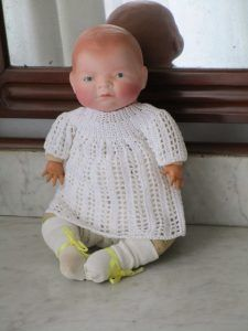 Baby Baby-lo with body of clothes and head of bisque (porcelain). The hands are celluloid. At the nape of the neck is branded Copy Grace Putman Made Germany.