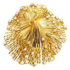 An 18 kt gold and diamond brooch designed as an open wire spray with knot motif . circa 1960s