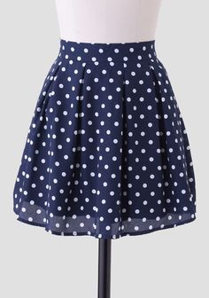 A Ruchette must-have, this smooth-as-silk navy skirt is adorned with a classic white polka dot print. Perfected with pleats for added flare and an exposed back zipper closure, this charming skirt...