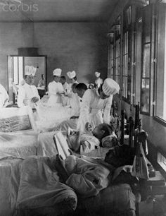 Nurses aid bedridden Japanese soldiers wounded during the Russo-Japanese War, 1904-1905.