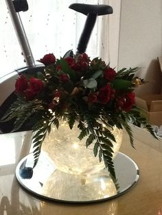 Red Christmas centrepiece. Bubble bowl with cellophane in water. Topped with red rose and hypericum berries. Take 2 with the lights out