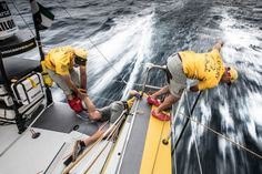 "March, 2015. Leg 5 to Itajai onboard Abu Dhabi Ocean Racing. Day 01. Justin Slattery is pushing debris off the leeward rudder as Simon ""SiFI"" Fisher holds the leg of Luke ""Parko"" Parkinson as he leans out to help clean - Matt Knighton / Abu Dhabi Ocean Racing / Volvo Ocean Race"