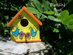 """Sunny Day Bird House, by Benita Sweeney of """"Blackbird Moon Art"""" Etsy shop $15. For display outdoors or in! Each of the little birdhouses I paint are unique and feature bright folk art designs painted completely freehand. Cheerful and bright, this little birdhouse is sunny yellow with a bright orange roof. It is painted with a primitive style design of happy bluebirds, flowers and butterflies.  ~  outdoor garden art"""