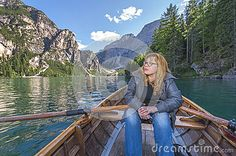 Young woman with oars at the picturesque lake. The Dolomite Alps. Italy